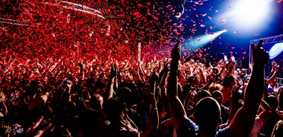 Nightclub party clubbers with hands in air and red confetti