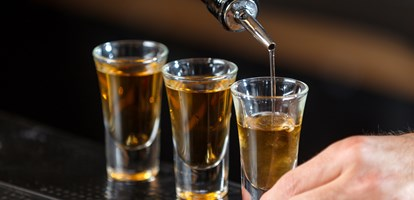 Close up photo of hands of a bartender pouring some drink into shot glasses on a wooden counter