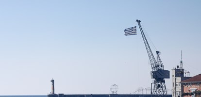 Greek flag on a crane seen in Thessaloniki, Greece, on the iconic pier of the old port