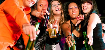 Group of friends - men and women of different ethnicity - having fun in a disco or nightclub