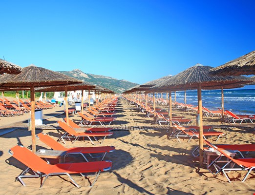 Rows of straw umbrellas and loungers at banana beach, Zakynthos, Greece.
