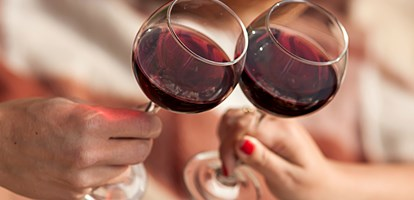 Man and woman drinking red wine. In the picture, close-up hands with glasses.