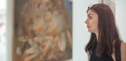 Young woman looking at modern painting in art gallery