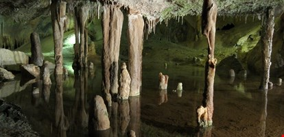 Stalactites, stalagmites and transparent underground lake in Can Mark Cave, Port de Sant Miguel, Ibiza, Spain